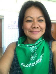 """Foto de Argentina Casanova portando un pañuelo verde con la leyenda """"Aborto Legal Ya""""."""